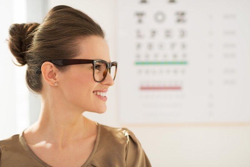Happy young woman wearing eyeglasses in front of Snellen chart