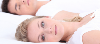 Woman sleeping with eyes open near sleeping spouse.