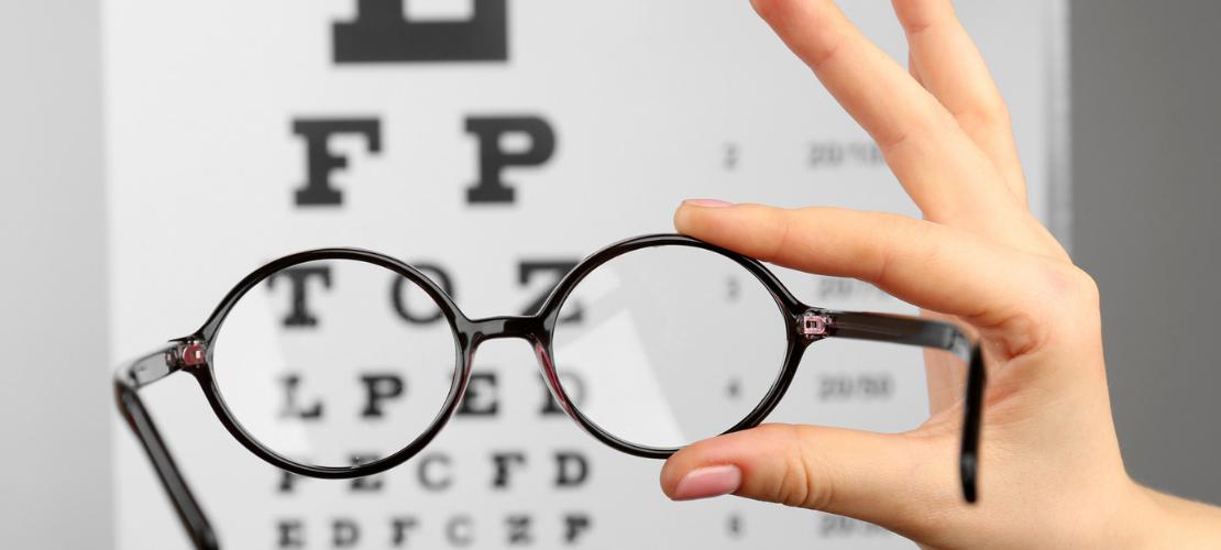 Eyeglasses in front of Snellen eye chart