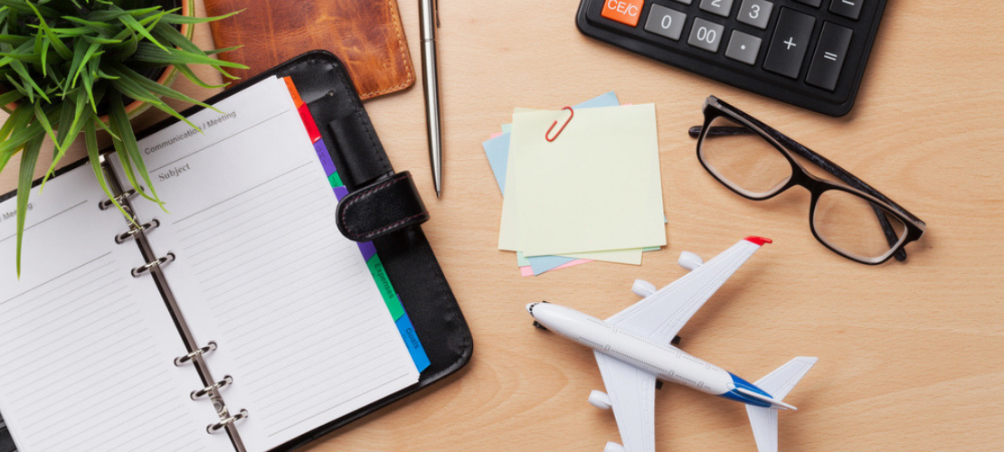 Eyeglasses on a desk with a planner, notes and a toy airplane.