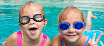 Little girls swimming with goggles