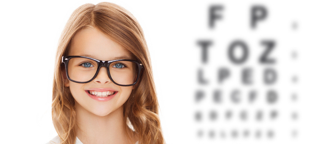 Kid wearing glasses with eye chart
