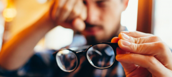 Sudden vision changes causing blurry vision with man holding glasses